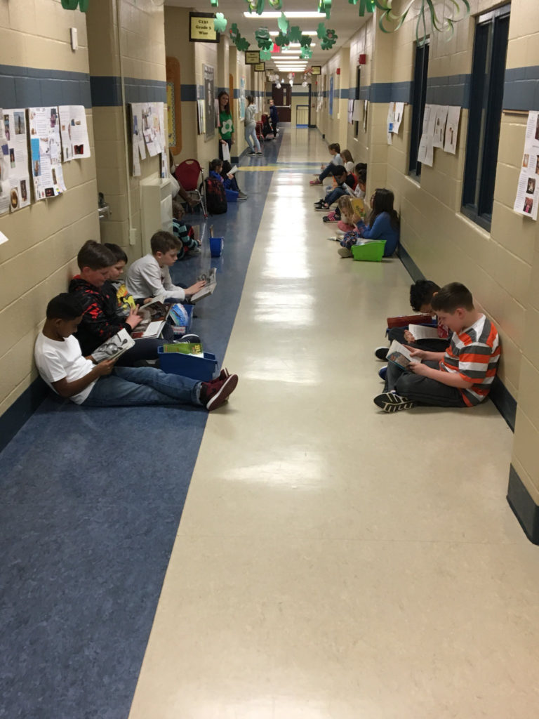 students reading in a hallway